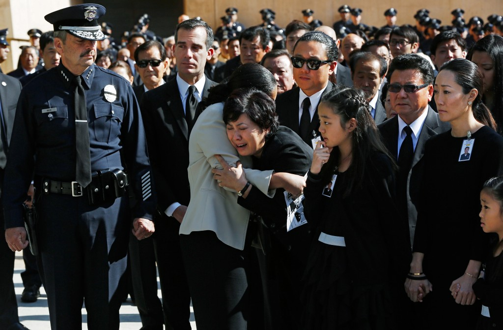 Choung Ja Lee, mother of fallen Los Angeles Police Department Nicholas Choung Lee, fourth from left, is helped by a LAPD female police officer, as her son's casket leaves a funeral mass at the Cathedral of Our Lady of the Angels in Los Angeles Thursday, March 13, 2014. Others from left include Los Angeles Police Chief Charlie Beck, Mayor Eric Garcetti, Lee's daughter Jalen, middle front, brother Danny, center rear, father Heung Jae Lee, and wife Cathy Kim, right.  Lee, 40, died when the squad car he and his partner were in collided with a trash truck in Beverly Hills on March 7. (AP Photo/Damian Dovarganes)