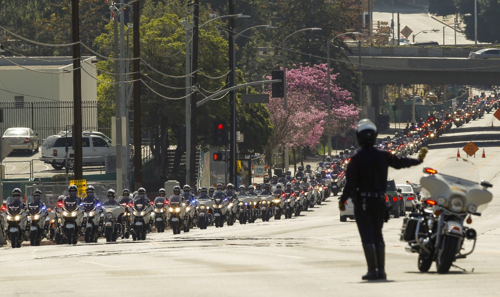 A motorcade of Los Angeles police officers escorts a hearst carrying the casket of fallen LAPD Officer Nicholas Choung Lee after his funeral mass at the Cathedral of Our Lady of the Angels in Los Angeles, Thursday, March 13, 2014. Lee, 40, died when the squad car he and his partner were in collided with a trash truck in Beverly Hills on March 7. (AP Photo/Damian Dovarganes)