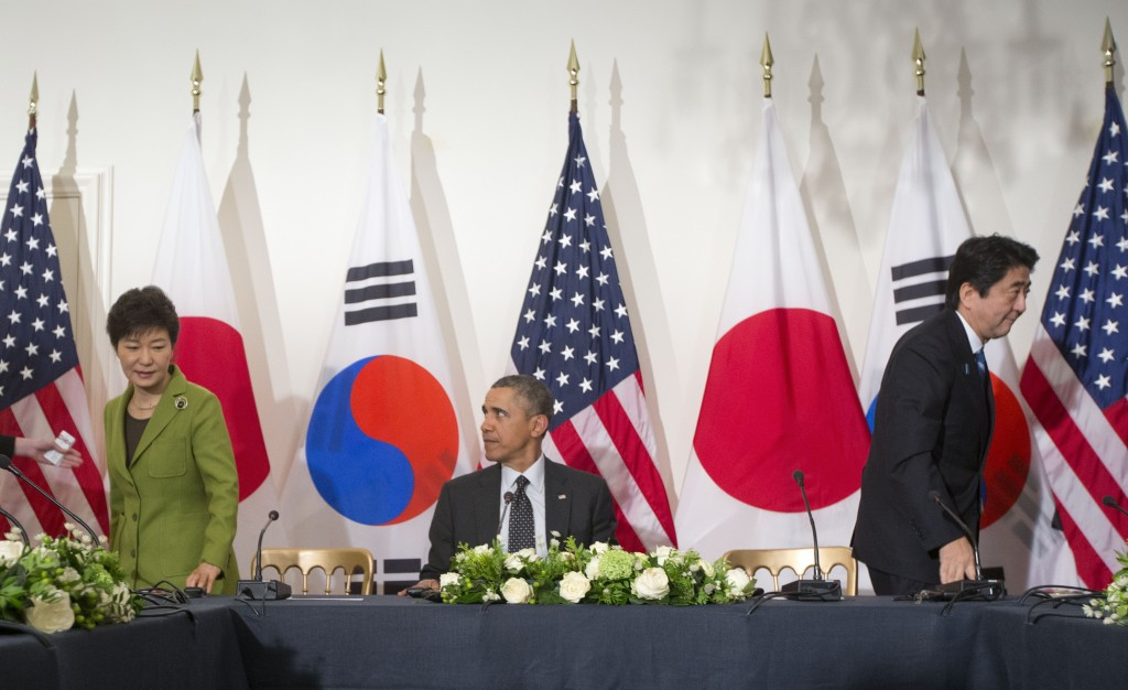 President Barack Obama watches as South Korean President Park Geun-hye, left, and Japanese Prime Minister Shinzo Abe, leave their seats at the opposite ends of the table, Tuesday, March 25, 2014, during the start of their trilateral meeting at the US Ambassador's Residence in the Hague, Netherlands. (AP Photo/Pablo Martinez Monsivais)