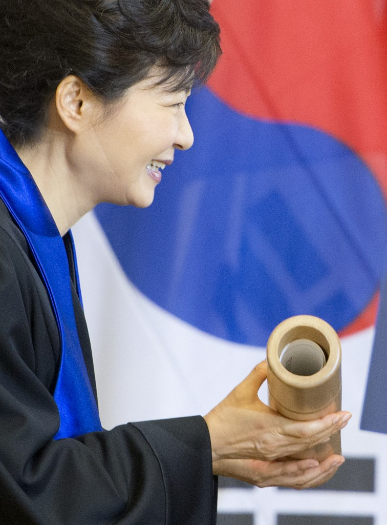 South Korean President Park Geun-hye holds the honorary doctorate document she received during a ceremony at the Dresden University of Technology in Dresden, Germany, Friday, March 28, 2014. (AP Photo/Jens Meyer)