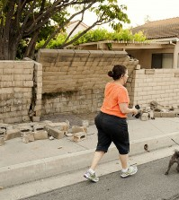 A woman walks her dog past a broken block wall in Fullerton, Calif., on Saturday, March 29, 2014,  after an earthquake hit Orange County Friday night. More than 100 aftershocks have rattled Orange County south of Los Angeles where a magnitude-5.1 earthquake struck Friday.  Despite the relatively minor damage, no injuries have been reported. (AP Photo/The Orange County Register, Ken Steinhardt)
