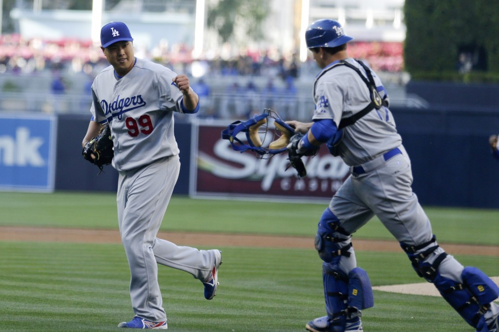 Dodgers starting pitcher Ryu Hyun-Jin, left, celebrates with catcher A.J. Ellis after getting the last out on the San Diego Padres  during the first inning of an opening night baseball game Sunday, March 30, 2014, in San Diego. (AP Photo/Gregory Bull)