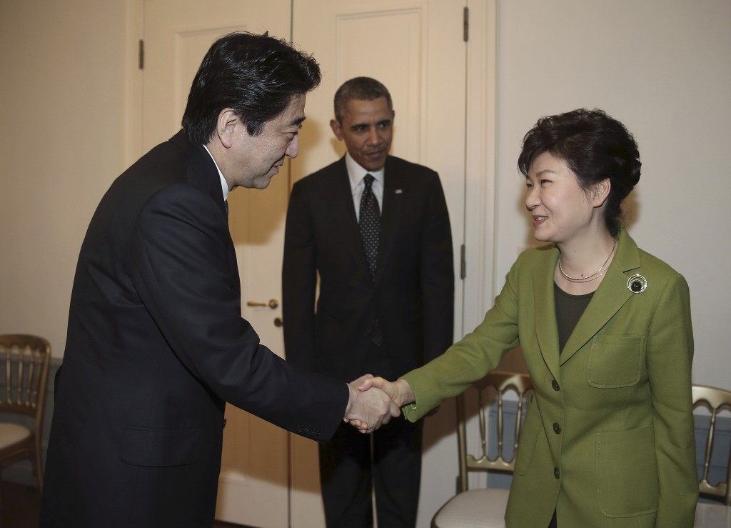South Korean President Park Geun-hye, right, shakes hands with Japanese Prime Minister Shinzo Abe, left, as US President Barack Obama looks on before their trilateral meeting at the US Ambassador's Residence in the Hague, Netherlands, Tuesday, March 25, 2014. (AP Photo/Yonhap, Do Kwang-hwan)