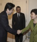 South Korean President Park Geun-hye, right, shakes hands with Japanese Prime Minister Shinzo Abe, left, as US President Barack Obama looks on before their trilateral meeting at the US Ambassador's Residence in the Hague, Netherlands, Tuesday, March 25, 2014. (AP)
