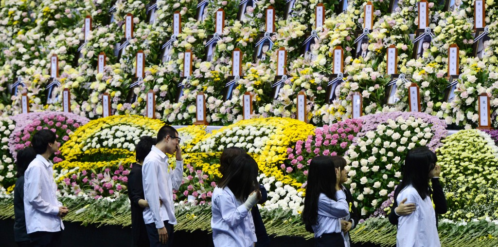 Danwon High School students rescued from the sunken ferry Sewol are overwhelmed with emotion while passing an array of photographs of their fellow students who didn't survive during their trip to a joint memorial altar set up in Ansan Hwarang Park, Gyeonggi Province, Wednesday. (Yonhap)