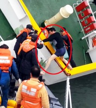 Sewol Captain Lee Joon-seok in his underwear is being rescued from the ship as it capsizes by first responders in this still from a video capturing the sinking of the ferry on April 16, which was released by the Coast Guard, Monday. While Lee and other crewmembers were taking flight, other footage shows few people on the decks, with hundreds of students heeding the crew's instructions and staying inside their cabins. Over 300 people, mostly students on a school trip, have been confirmed dead or listed as missing. / Yonhap