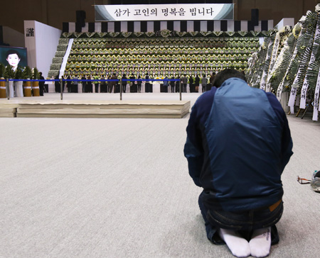 """So sorry. We've failed you..."" - A man kneels with his head bowed before a group memorial altar for Danwon High School students who died in the sinking of the ferry Sewol, at the Ansan Olympic Museum Gymnasium, Thursday. The temporary altar will be open until April 28 before an official altar is set up on April 29 at Ansan Hwarang Park. (Yonhap)"