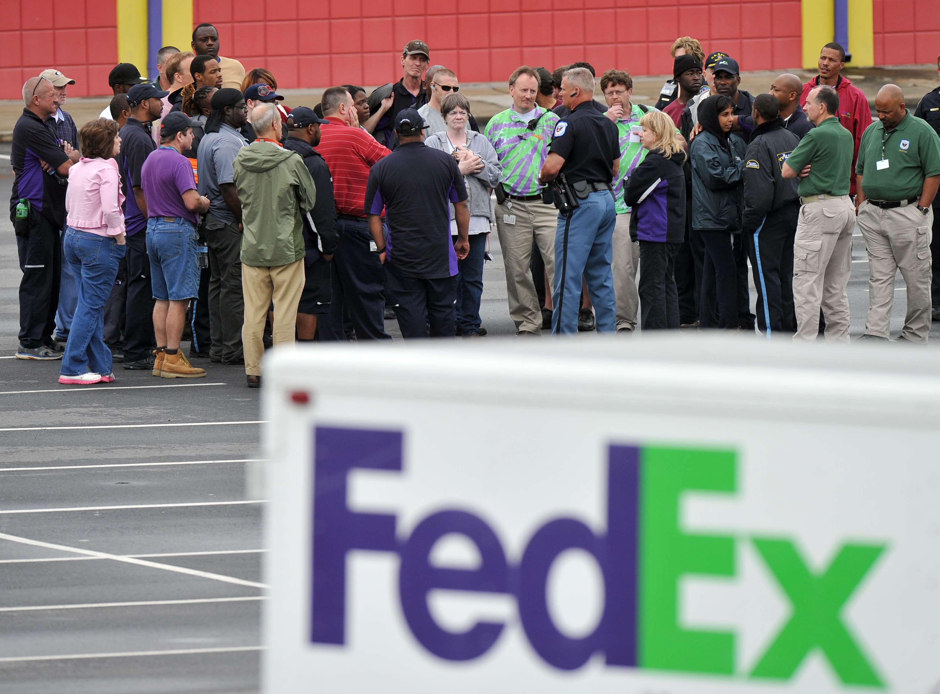 """A Cobb County Police Officer speaks to FedEx employees and family members gathered at the parking lot of a skating rink located near the shipping facility where a gunman open fire in Kennesaw, Ga., on Tuesday, April 29, 2014.  A shooter described as being armed with an assault rifle and having bullets strapped across his chest """"like Rambo"""" opened fire Tuesday morning at a FedEx station outside Atlanta, wounding at least six people before police found the suspect dead from an apparent self-inflicted gunshot.  (AP Photo/Atlanta Journal-Constitution, Brant Sanderlin)"""