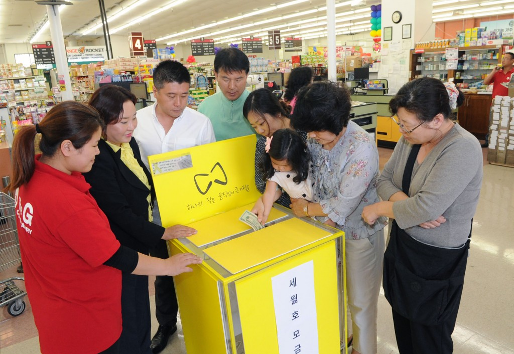 A child puts money into the donation box set up at Kaju Market. / Park Sang-hyuk, The Korea Times