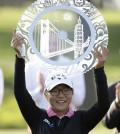Lydia Ko of New Zealand holds up her trophy on the 18th green of the Lake Merced Golf Club after winning the Swinging Skirts LPGA Classic golf tournament on Sunday, April 27, 2014, in Daly City, Calif. Ko won the event after shooting a 3-under-par 69 to finish at 12-under-par. (AP Photo/Eric Risberg)