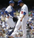 Los Angeles Dodgers starting pitcher Hyun-Jin Ryu, right, of South Korea, talks with catcher A.J. Ellis during the second inning of a baseball game against the San Francisco Giants on Friday, April 4, 2014, in Los Angeles. (AP Photo/Jae C. Hong)