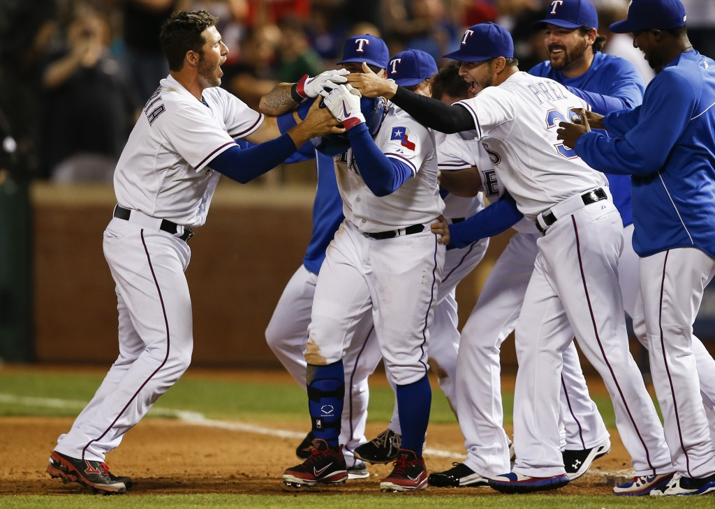 Texas Rangers' Shin-Soo Choo, center, is swarmed by teammates including J.P. Arencibia, left, and Martin Perez, right, after drawing a bases-loaded game-winning walk in a baseball game against the Philadelphia Phillies, Wednesday, April 2, 2014, in Arlington, Texas. The Rangers won 4-3. (AP Photo/Jim Cowsert)