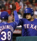 Texas Rangers manager Ron Washington (38) congratulates Shin-Soo Choo for hitting a solo home run against the Los Angeles Angels in the sixth inning of a baseball game on Friday, May 2, 2014, in Anaheim, Calif. (AP Photo/Alex Gallardo)