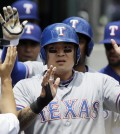 Texas Rangers' Shin-Soo Choo is greeted in the dugout after scoring on a double by Adrian Beltre during the third inning of a baseball game against the Detroit Tigers in Detroit, Thursday, May 22, 2014. Choo homered, Chris Gimenez had four hits and the Rangers rolled to a 9-2 victory over the Tigers. (AP Photo/Carlos Osorio)