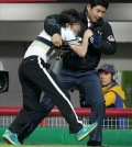 A fan is being forced out of Gwangju-Kia Champions Field on April 30, 2014, after attacking an umpire during a game between the home team Kia Tigers and the visiting SK Wyverns. (Yonhap)