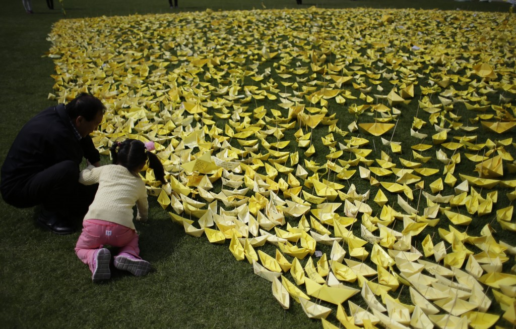 A girl with a man put a paper ship for the victims and missing passengers of the sunken ferry Sewol at a group memorial altar in Seoul, South Korea, Wednesday, May 7, 2014. (AP Photo/Lee Jin-man)