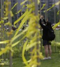 A girl ties yellow ribbons with messages for missing passengers aboard the sunken ferry boat Sewol in the water off the southern coast, in Seoul, South Korea, Friday, May 2, 2014. More than 300 people are dead or missing in the disaster that has caused widespread grief, anger and shame. (AP Photo/Lee Jin-man)
