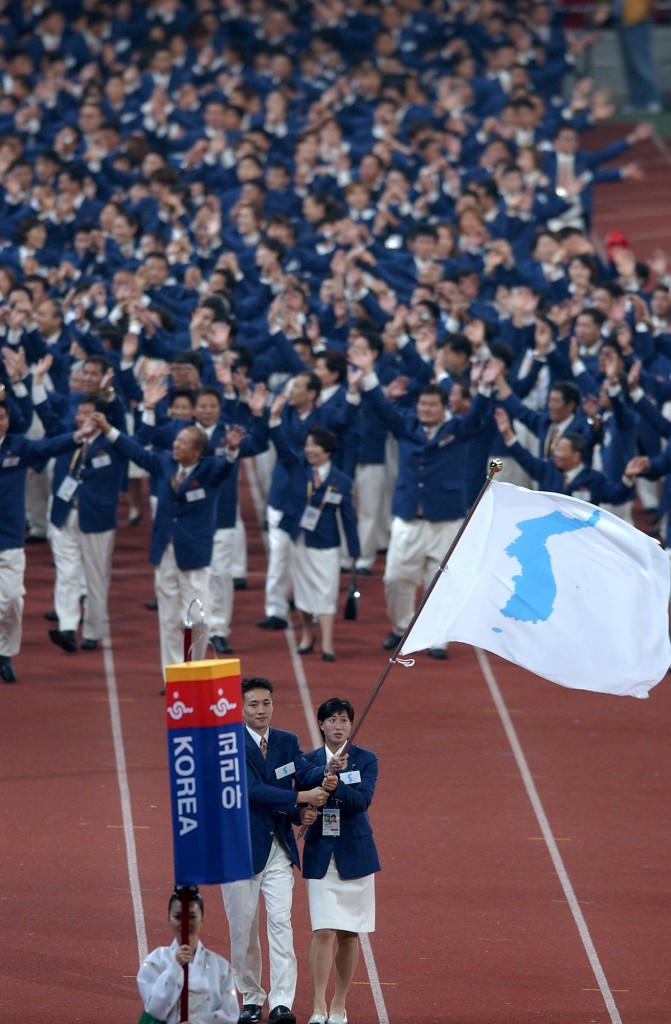 Koreas have entered international competition arena together before, as shown here in the opening ceremony of the Busan Asian Games in 2002.  South Korean handball player Hwangbo Sung-il, left, and North Korean female soccer player Li Jung-hee are holding up the 'One Korea' flag together. (Yonhap)