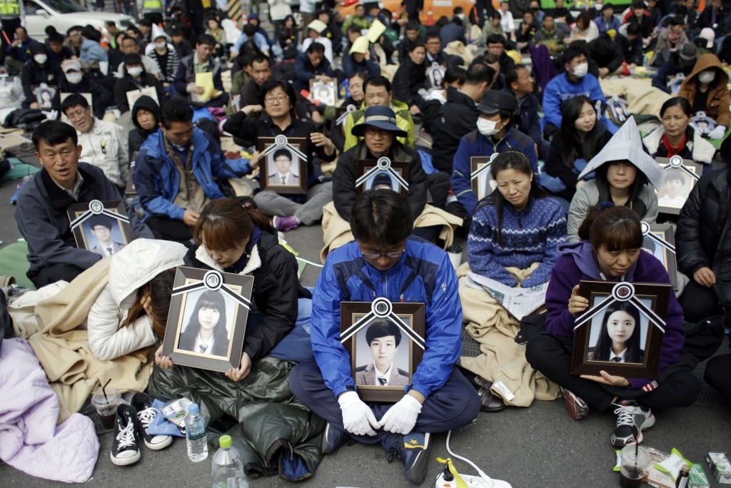 Family members holding the portraits of the victims of the sunken ferry Sewol, sit on the street near the presidential Blue House in Seoul, South Korea, Friday, May 9, 2014.