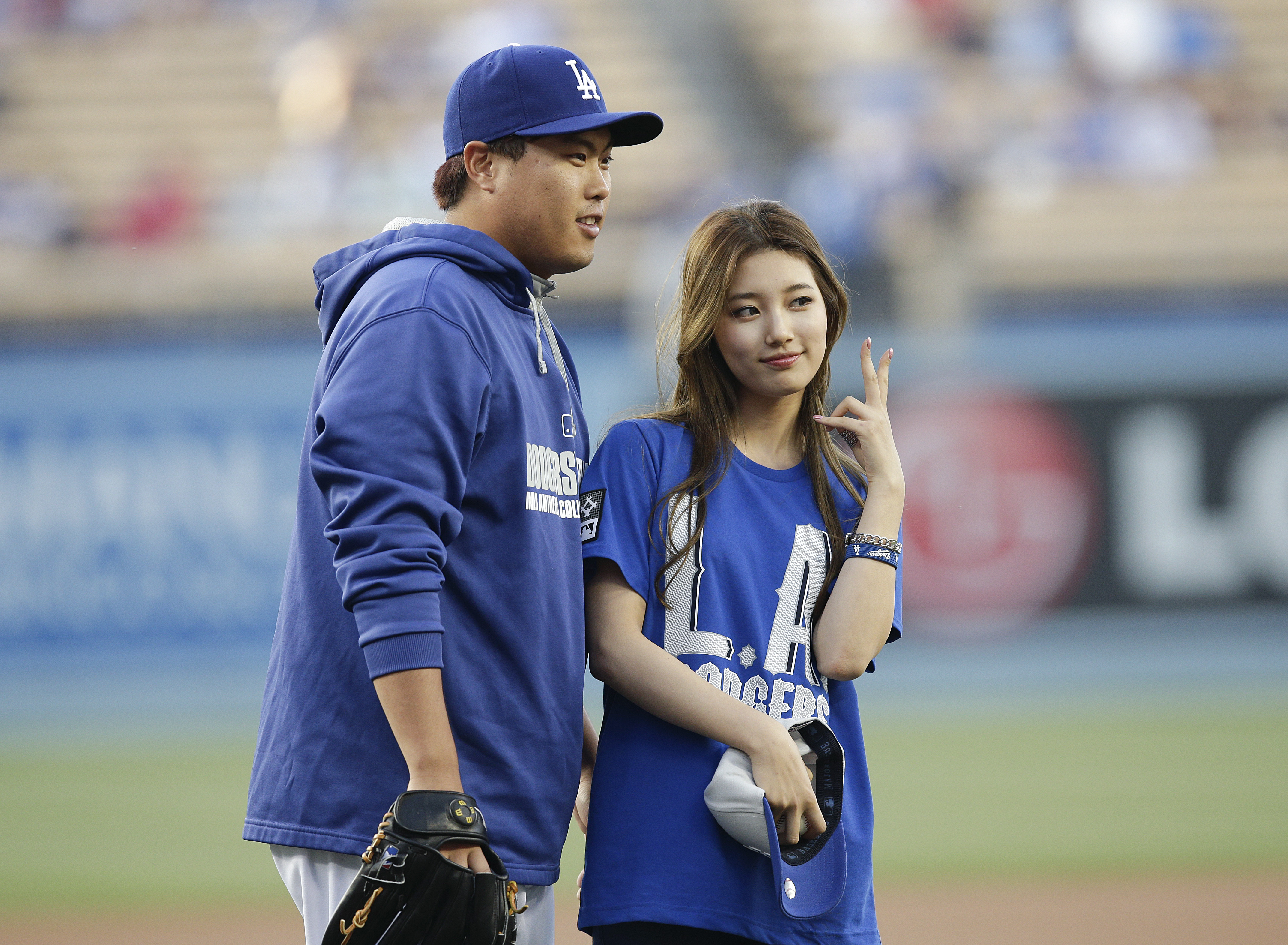 Los Angeles Dodgers starting pitcher Hyun-Jin Ryu, left, of South Korea, poses with South Korean singer Suzy after she threw the ceremonial first pitch before the team's baseball game against the Cincinnati Reds on Wednesday, May 28, 2014, in Los Angeles. (AP Photo/Jae C. Hong)