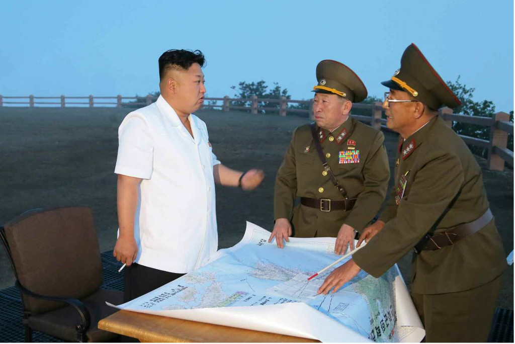 This Rodong Sinmun photo released on June 30, 2014, shows North Korean leader Kim Jong-un talking to military officials during a tactical rocket firing drill of the North's Strategic Force at an unidentified place.   (Yonhap)