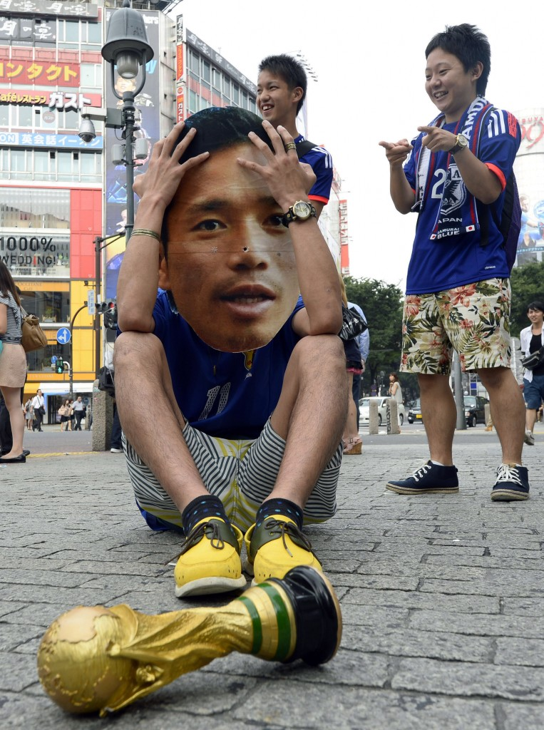 A Japanese soccer fan wearing a mask of Japanese soccer player Yuto Nagatomo sits on a street after the group C World Cup soccer match between Japan and Colombia outside a public viewing venue in Tokyo early Wednesday, June 25, 2014. For Japan, this World Cup has been a nightmare revisited: The Asian champions seize momentum with waves of dangerous attack, and little payoff. Then their opponent's talismanic player comes on as a second-half substitute - and Japan wilts under pressure. (AP Photo/Kyodo News)