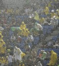 Spectators sit under pouring rain as they watch the group A World Cup soccer match between Mexico and Cameroon in the Arena das Dunas in Natal, Brazil, Friday, June 13, 2014.  (AP Photo/Hassan Ammar)