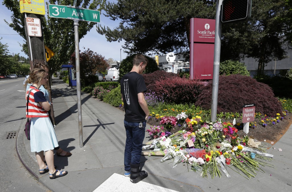 Students view a growing memorial at Seattle Pacific University near Otto Miller Hall Friday, June 6, 2014 in Seattle, where a fatal shooting took place Thursday afternoon. (AP Photo/Ted S. Warren)