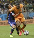 Japan's Masato Morishige, left, tries to hold Ivory Coast's Didier Drogba, right, during the group C World Cup soccer match at the Arena Pernambuco in Recife, Brazil, Saturday, June 14, 2014. (AP Photo/Petr David Josek)
