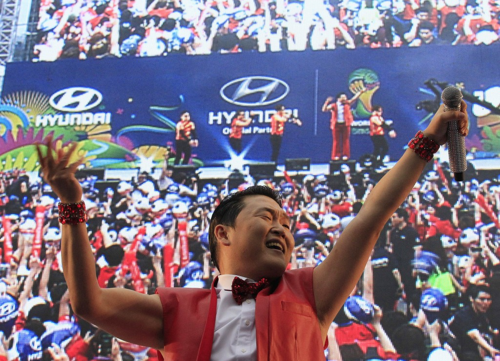 South Korean rapper PSY performs before a TV broadcasting 2014 Brazil World Cup Group H game between South Korea and Russia at a public viewing venue in Seoul, South Korea, Wednesday, June 18, 2014.(AP Photo/Ahn Young-joon)