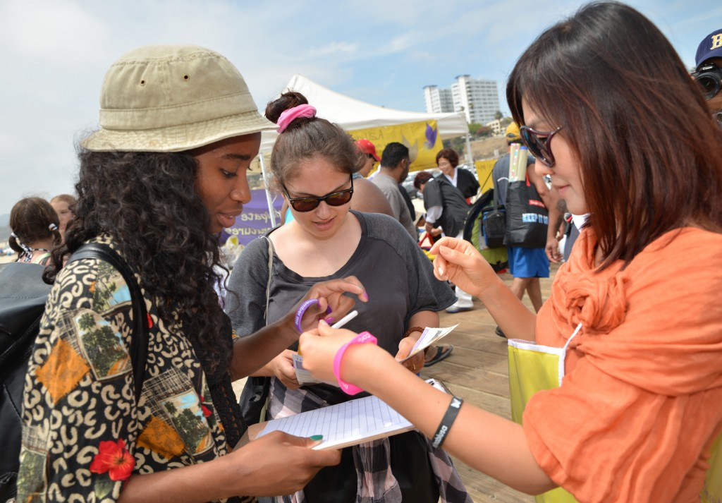 A Nabi USA member collects signatures from passerby at Santa Monica Pier for the 100 Million Signatures Campaign on June 21. (Kim Young-jae / The Korea Times)