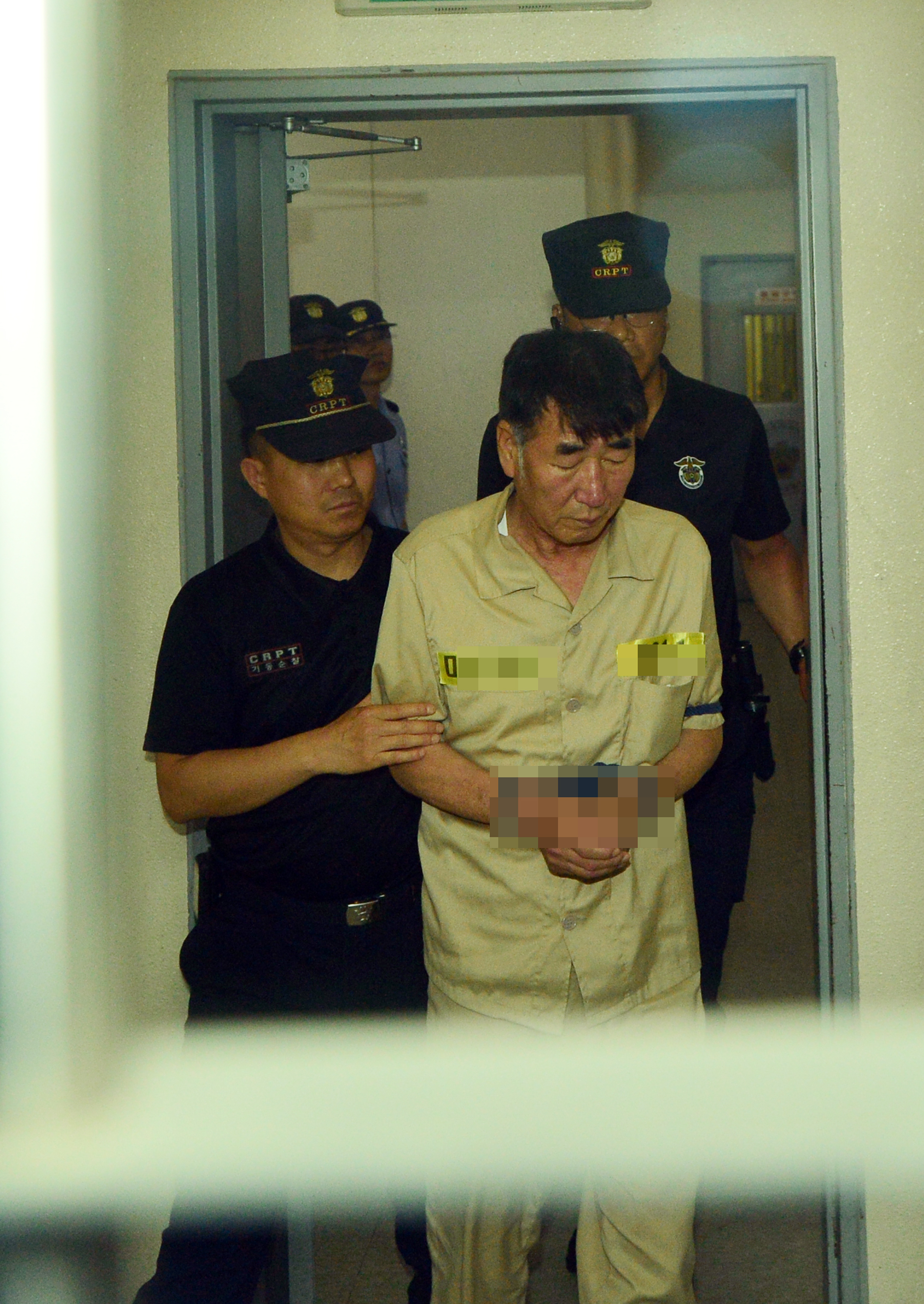 Lee Joon-seok, the captain of the sunken ferry Sewol, is taken to a courtroom for the first hearing of his murder trial, Tuesday. (Yonhap)