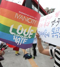 "A woman, right, holds up a sign that reads, ""Both parents are men, both parents are women. Our children are crying,"" beside an event supporter at the annual Korea Queer Festival (KQF) last week in Sinchon, northwestern Seoul. (Yonhap)"