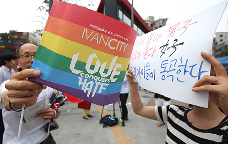 "A woman, right, holds up a sign that reads, ""Both parents are men, both parents are women. Our children are crying,"" beside an event supporter at the annual Korea Queer Festival (KQF) last week in Sinchon, northwestern Seoul. ( Yonhap)"