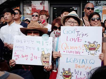 A participant in the 15th Korea Queer Festival holds a placard supporting the rights of lesbian, gay, bisexual and transgender (LGBT) people in Sinchon, western Seoul, Saturday.  (Nam Hyun-woo / Korea Times)