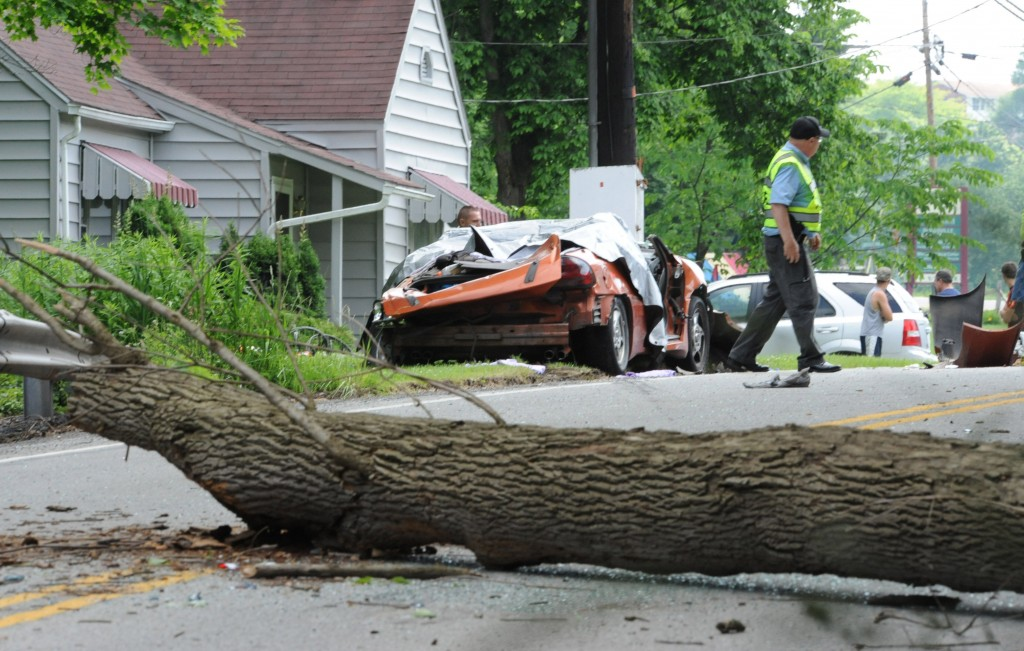 "Conemaugh Township Police Chief Louis ""Pete"" Barclay surveys the scene of a double fatality caused by a large dead tree that fell directly onto a car carrying two adults (one pregnant) and four children on SR403 near Tire Hill, PA., Mon., June 23, 2014.  In Canada last Tuesday, a Korean couple from Baltimore also got killed when a storm caused a tree to fall on their car.  (AP )Photo/Tribune-Democrat, John Rucosky)."