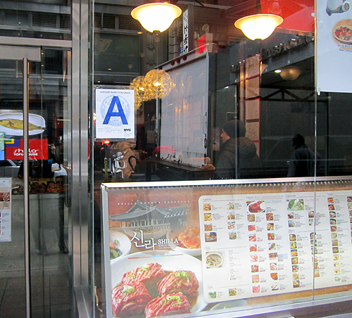 "A Korean restaurant in New York City displays its ""A"" inspection grade on its front window."
