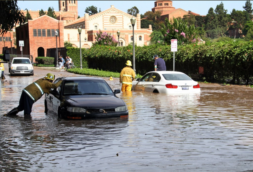 Los Angeles firefighters help drivers whose cars became stranded on Sunset Boulevard after a 30-inch water main broke and sent water flooding down Sunset and onto the UCLA campus, background, in the Westwood section of Los Angeles on Tuesday, July 29, 2014.(AP Photo/Steve Gentry)