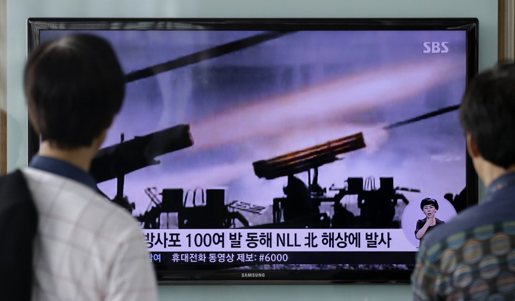 "People watch a TV news program reporting on North Korea's artillery shells at Seoul Railway Station in Seoul, South Korea, Monday, July 14, 2014. North Korea on Monday fired artillery shells into waters near its sea border with South Korea, Seoul's military said, a day after the country test-launched two ballistic missiles in the latest of a series of weapon tests. The superimposed letters on the screen read: "" North Korea fired about 100 artillery shells into NLL North Korea area on east sea"".  (AP Photo/Lee Jin-man)"