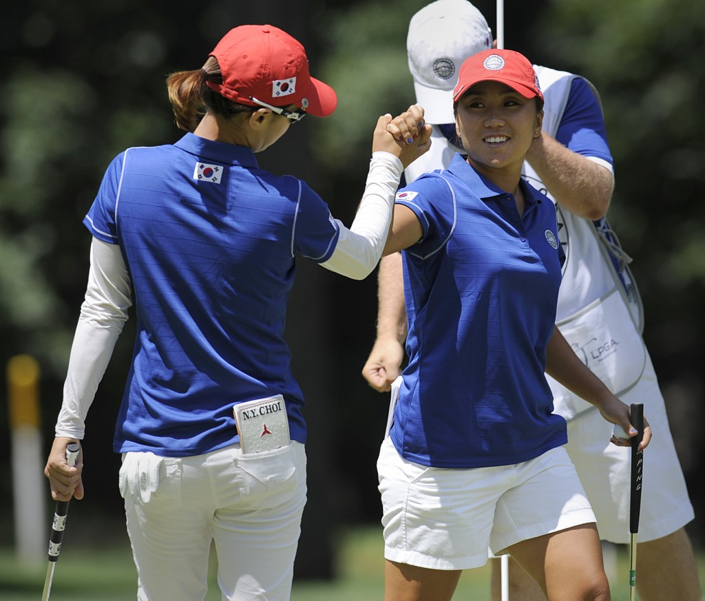 Na Yeon Choi, left, and I.K. Kim, both of South Korea, celebrate a birdie on the first hole during the third round of the International Crown golf tournament Saturday, July 26, 2014, in Owings Mills, Md.(AP Photo/Gail Burton)