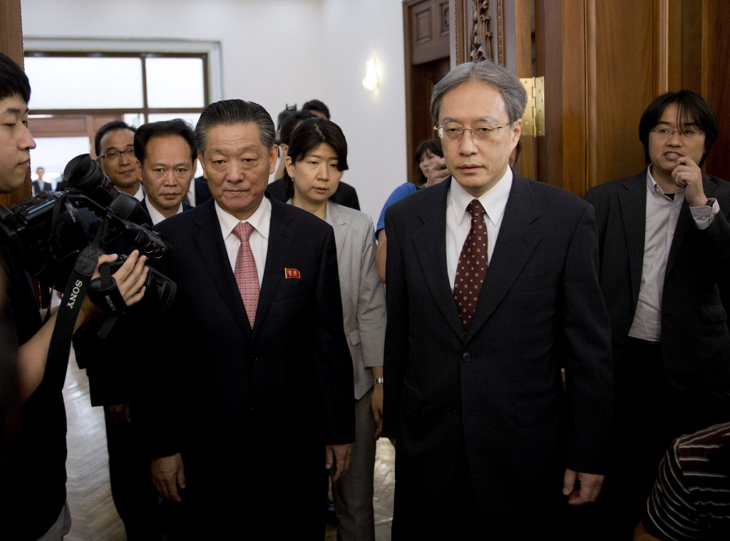 Song Il Ho, North Korea's ambassador in charge of normalizing relations with Japan, center left, and Junichi Ihara, head of the Japanese Foreign Ministry's Asian and Oceanian Affairs Bureau, center right, arrive for a meeting at the North Korean Embassy in Beijing, China Tuesday, July 1, 2014. (AP Photo/Andy Wong)