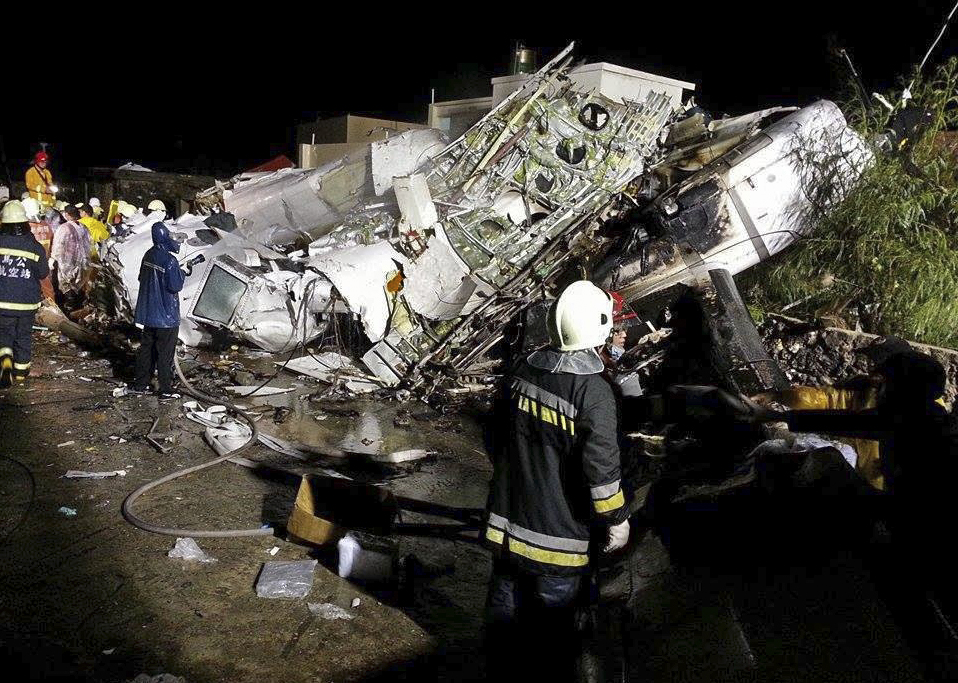 Rescue workers survey the wreckage of TransAsia Airways flight GE222 which crashed while attempting to land in stormy weather on the Taiwanese island of Penghu, late Wednesday, July 23, 2014. A transport minister said dozens of people were trapped and feared dead. (AP Photo/Wong Yao-wen)