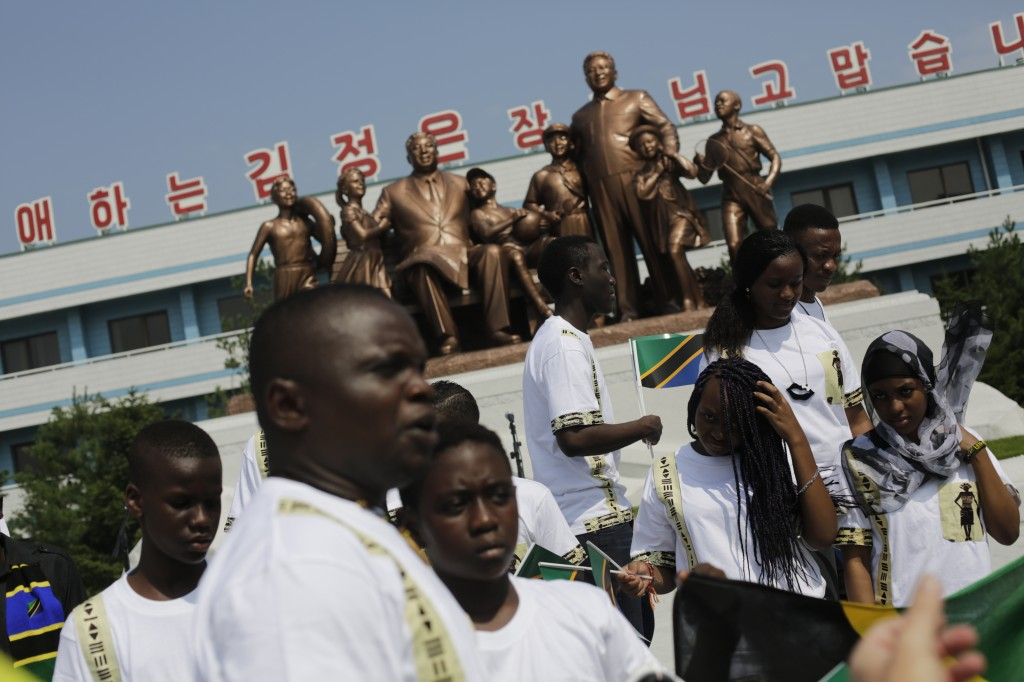 Students from the Laureat International School in Tanzania walk past a statue of the late North Korean leaders Kim Il Sung and Kim Jong Il, surrounded by children, on the parade square of the Songdowon International Children's Camp, Tuesday, July 29, 2014, in Wonsan, North Korea. The camp, which has been operating for nearly 30 years, was originally intended mainly to deepen relations with friendly countries in the Communist or non-aligned world.  (AP Photo/Wong Maye-E)
