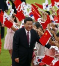 Chinese President Xi Jinping (C) and South Korean president Park Geun-hye (L) greets children waving the two national flags during a welcoming ceremony at the presidential Blue House in Seoul July 3, 2014.  (AP Photo/Kim Hong-ji, Pool)