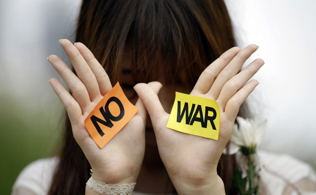 A South Korean students shows her palms with signs during a rally against the Israeli military operations in Gaza and the West Bank and wish for peace near the Israel Embassy in Seoul, South Korea, Wednesday, July 30, 2014. (AP Photo/Lee Jin-man)