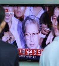 People watch a TV news program showing Yoo Byung-eun, the fugitive owner of the sunken ferry Sewol , at the Seoul Railway Station in Seoul, South Korea, Tuesday, July 22, 2014. South Korean police said Tuesday that a badly decomposed body of Yoo found surrounded by liquor bottles in a field last month was that of a fugitive billionaire businessman blamed for April's ferry disaster that killed more than 300 people.(AP Photo/Ahn Young-joon)