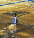 A worker begins the task of cleaning up at least an inch of water covering the playing floor at Pauley Pavilion, home of UCLA basketball, after a broken 30-inch water main under nearby Sunset Boulevard caused flooding that inundated several areas of the UCLA campus in the Westwood section of Los Angeles on Tuesday, July 29, 2014. (AP Photo/Mike Meadows)