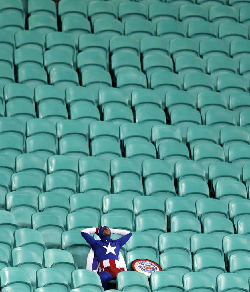A lone U.S. supporter dressed as 'Captain America' sits in the stands after Belgium defeated the U.S. 2-1 in extra time to advance to the quarterfinals during the World Cup round of 16 soccer at the Arena Fonte Nova in Salvador, Brazil, Tuesday, July 1, 2014. (AP Photo/Natacha Pisarenko, File)
