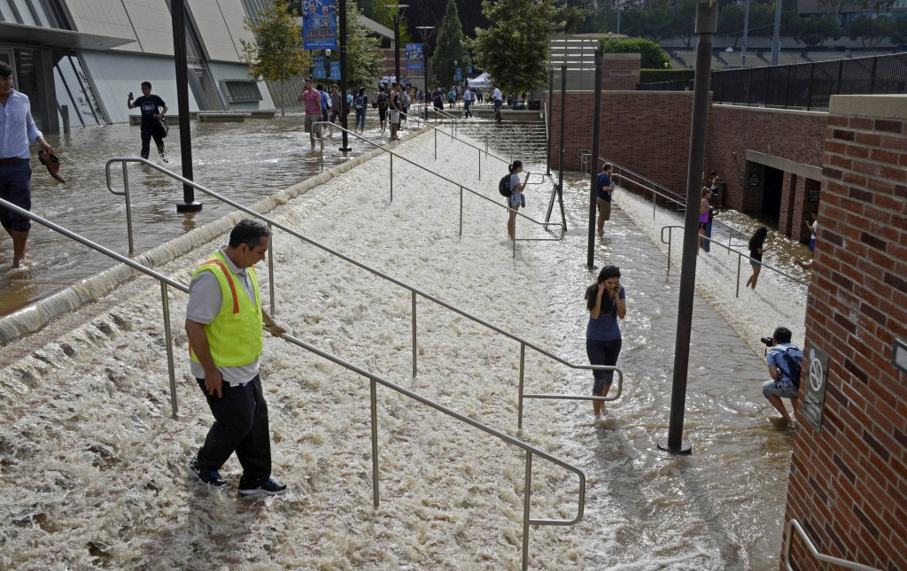 People walk down a stairway leading to a parking structure across from Pauley Pavilion on the UCLA campus after flooding from a broken 30-inch water main under nearby Sunset Boulevard inundated a large area of the campus in the Westwood section of Los Angeles, Tuesday, July 29, 2014. The 30-inch (75-centimeter)  93-year-old pipe that broke made a raging river of the street and sent millions of gallons (liters) of water across the school's athletic facilities, including the famed floor of Pauley Pavilion, the neighboring Wooden Center and the Los Angeles Tennis Center, and a pair of parking structures that took the brunt of the damage. (AP Photo/Mike Meadows)