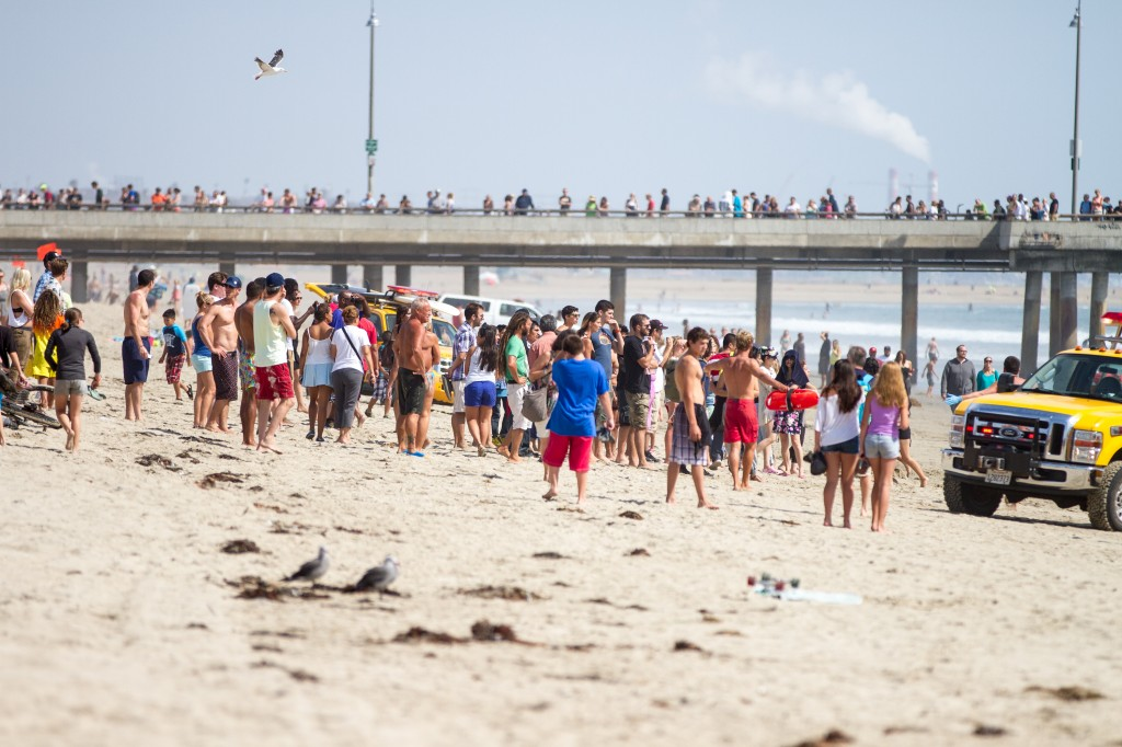 Pedestrians and beachgoers stand on the shore near Venice Beach as lifeguards, right, bring in a swimmer rescued from the water after a lightening strike Sunday July 27, 2014 in Los Angeles. Authorities said lightning struck 14 people, leaving two critically injured, as rare summer thunderstorms swept through Southern California on Sunday. (AP Photo/Steve Christensen)
